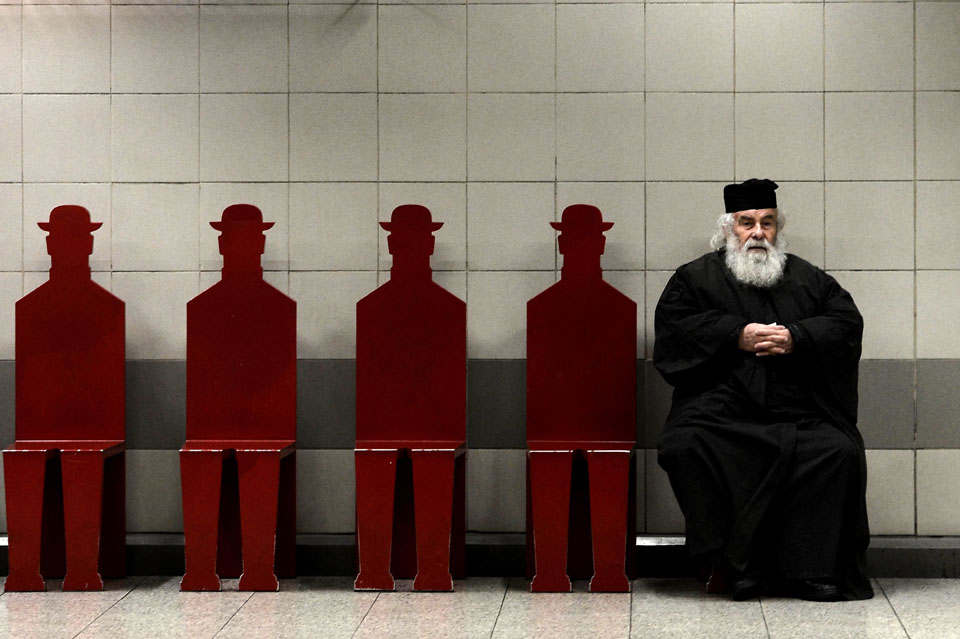 Greek Orthodox priest sits